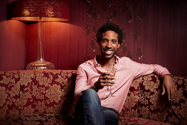 smiling man holding champagne flute at nightclub - club sofa stock-fotos und bilder