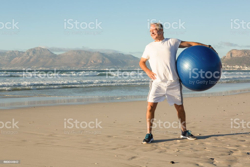 Smiling man holding exercise ball while standing at beach foto de stock royalty-free