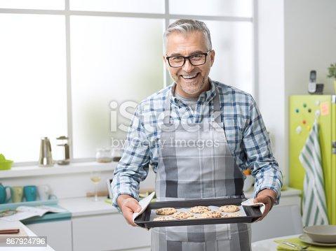 istock Smiling man holding freshly baked cookies 867924796