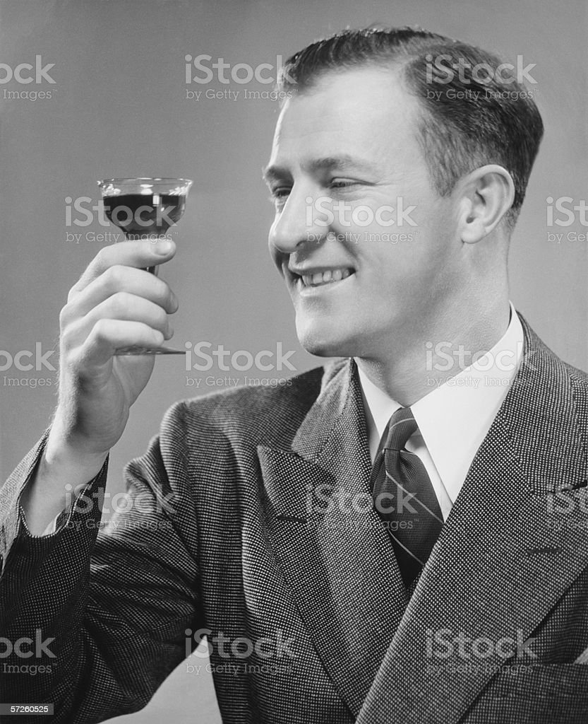 Smiling man holding up short glass with drink, (B&W), close-up royalty-free stock photo