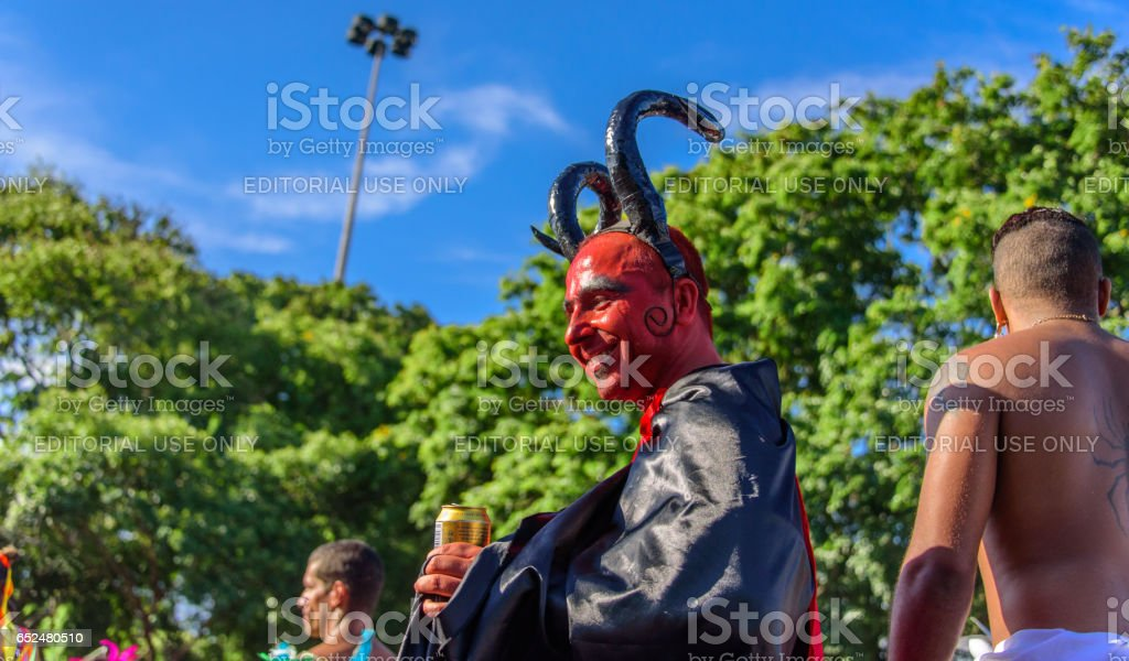 Smiling man in a costume of devil with red face, black horns and cloak walking on stilts at Bloco Orquestra Voadora, Carnaval 2017 stock photo