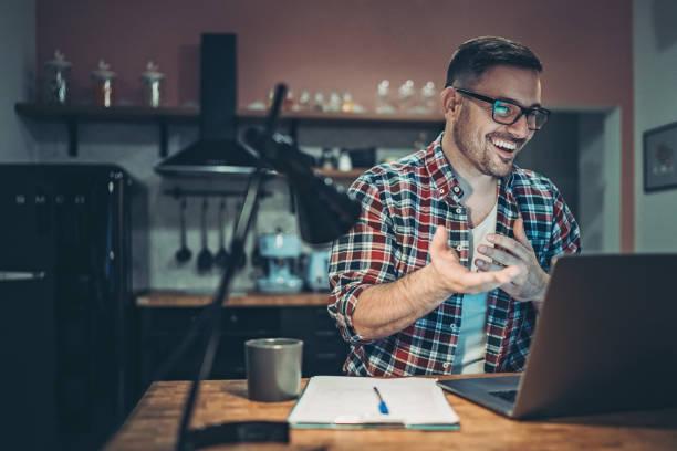 Lächelnder Mann in einem Videoanruf von zu Hause aus – Foto
