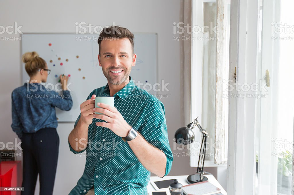 Smiling man in an office with cup of coffee Handsome man in an office, holding cup of coffee and smiling at camera. Back view of woman drawing on the board in the background. Adult Stock Photo