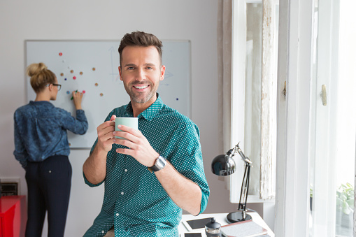 Smiling Man In An Office With Cup Of Coffee Stock Photo - Download Image Now