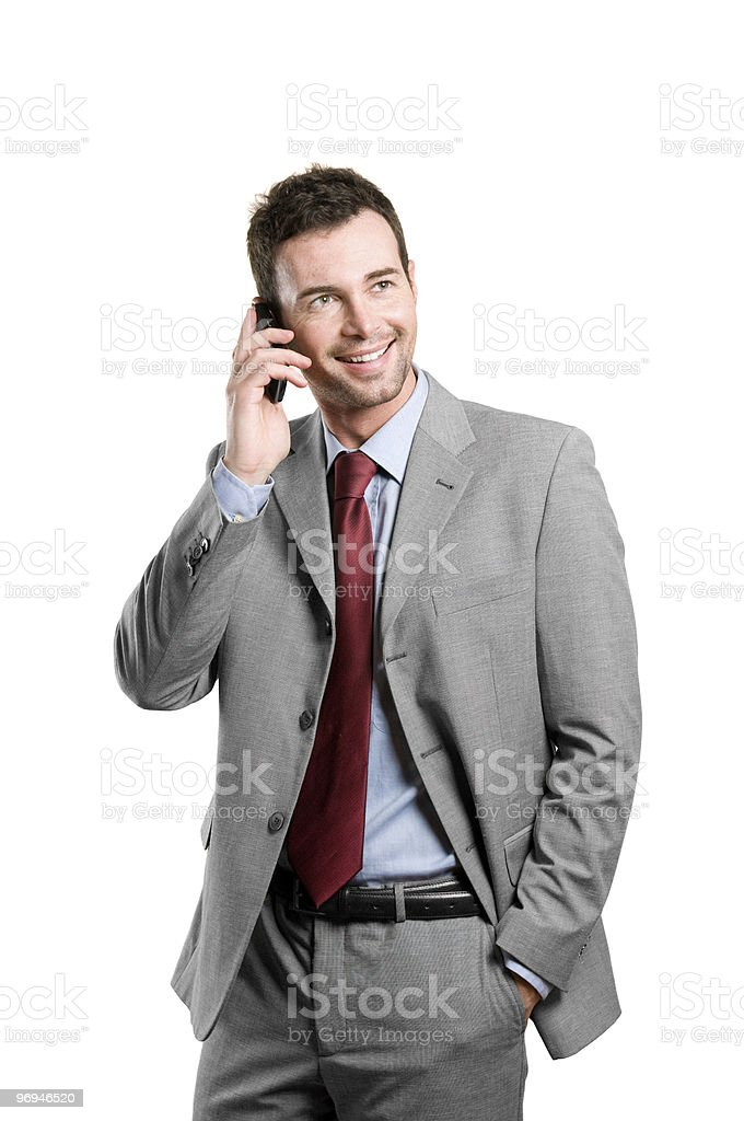 Smiling man in beige suit talking on his cellular phone royalty-free stock photo