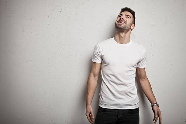 lächelnder mann im leeren t-shirt - druck jeans stock-fotos und bilder
