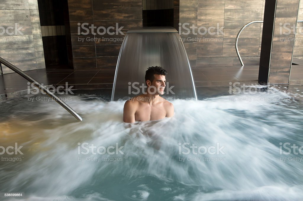 Smiling man in bubbled water stock photo