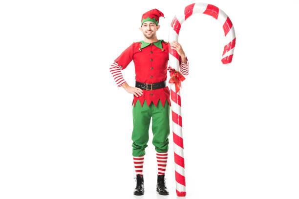 lächelnd mann in christmas elf kostüm mit der hand auf den hüften stehen in der nähe von großen candy cane isoliert auf weiss - faschingskostüme herren stock-fotos und bilder