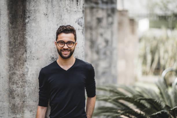 Homem sorridente em frente a parede de concreto - foto de acervo