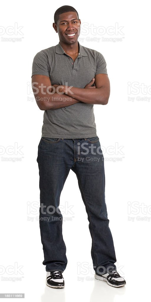 Smiling man in gray shirt and blue jeans with arms crossed stock photo