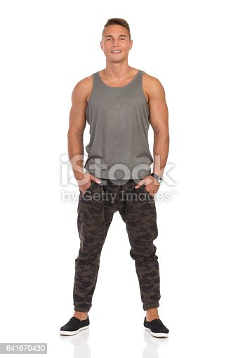 Smiling young muscular man in pants with camo, gray tank top and black sneakers standing with hands in pocket. Front view. Full length studio shot isolated on white.