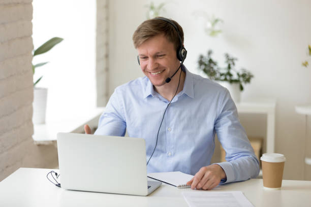 Smiling man in headphones making business video call Smiling man in headphones looking at computer screen watching webinar, making business video call, young businessman consulting remote client online writing notes, hr holding distance job interview remote control stock pictures, royalty-free photos & images