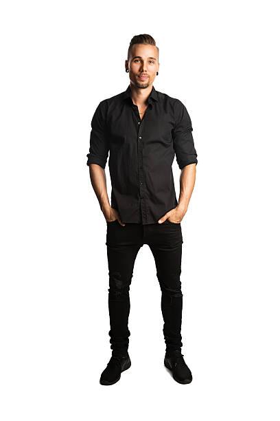 smiling man in jeans looking at camera - zwarte spijkerbroek stockfoto's en -beelden