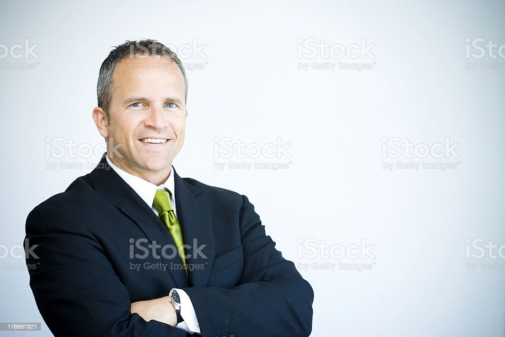 Smiling man in navy suit and green tie with arms crossed royalty-free stock photo