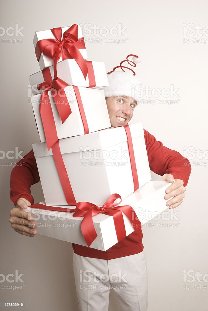 Smiling Man in Santa Hat Delivering Holiday Christmas Presents royalty-free stock photo
