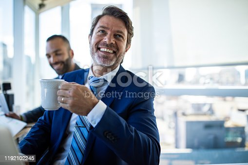 Joyful mature man in elegant suit and necktie sitting in office chair and drinking coffee