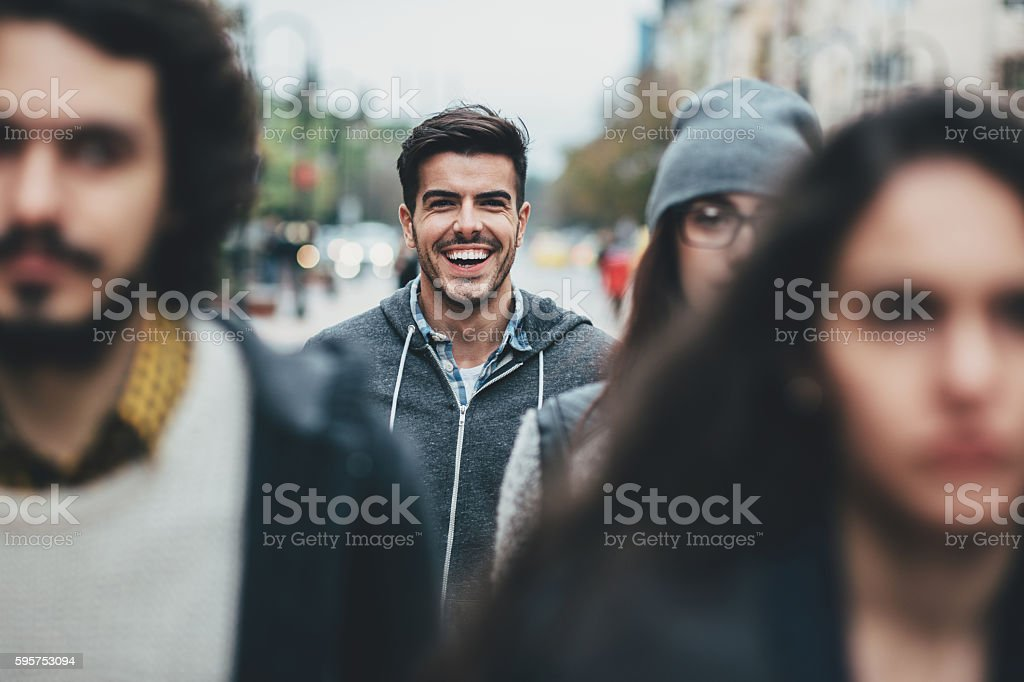 Smiling man in the crowd stock photo