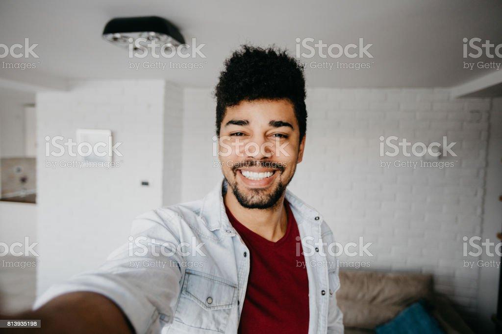 Homme dans la salle de séjour souriant prend un selfie - Photo