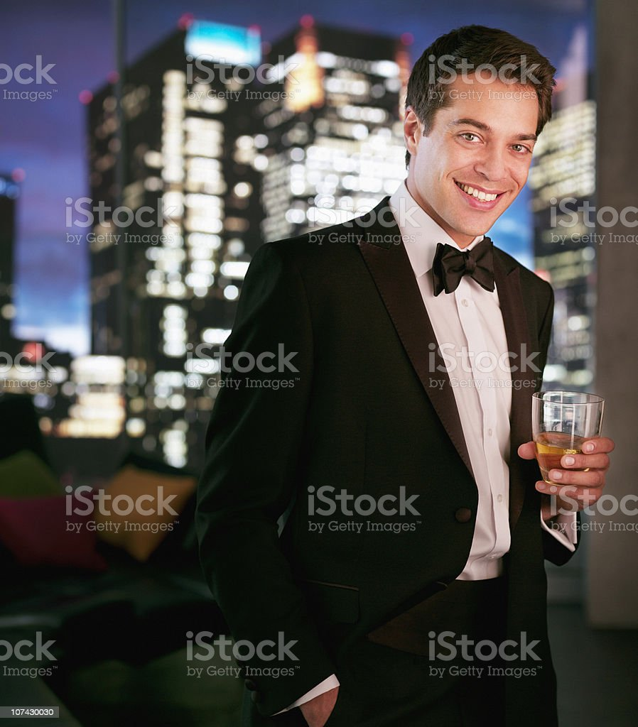 Smiling man in tuxedo drinking cocktail royalty-free stock photo