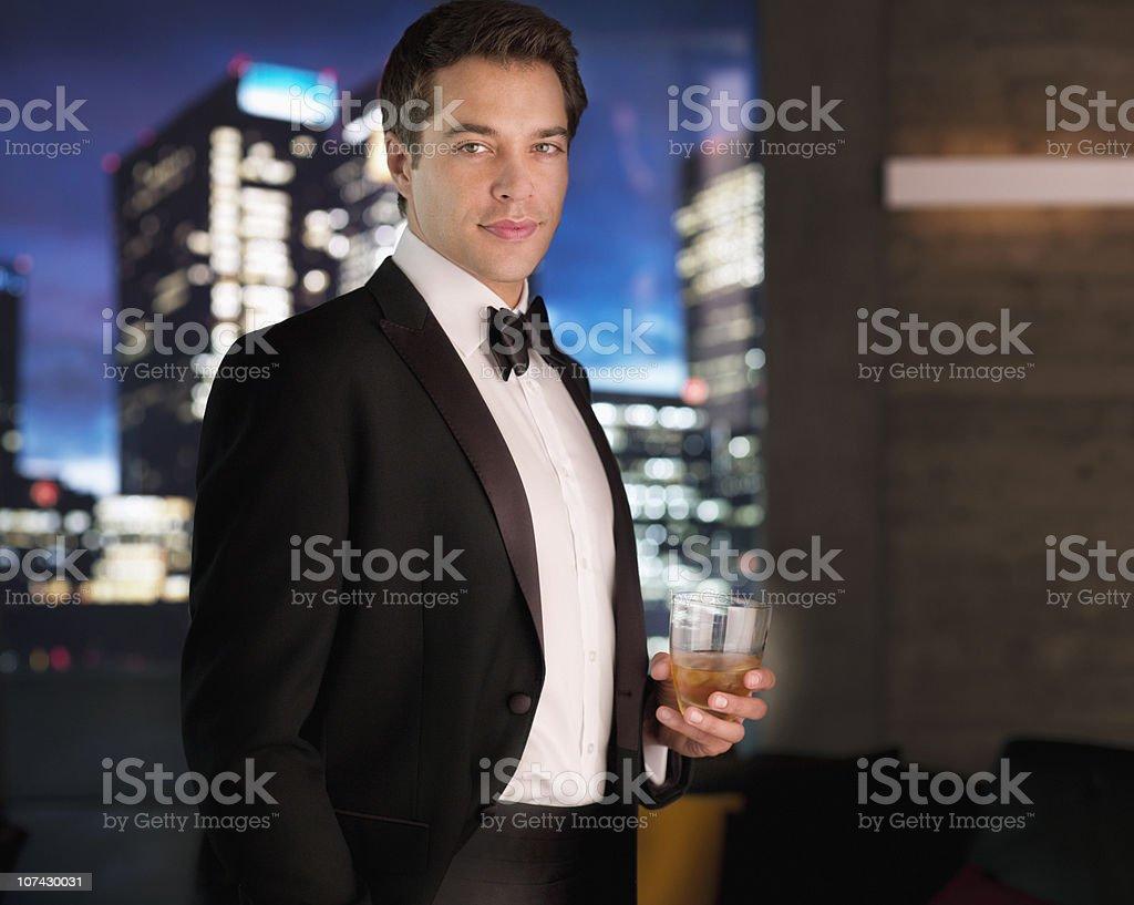 Homme souriant en smoking boire un cocktail - Photo
