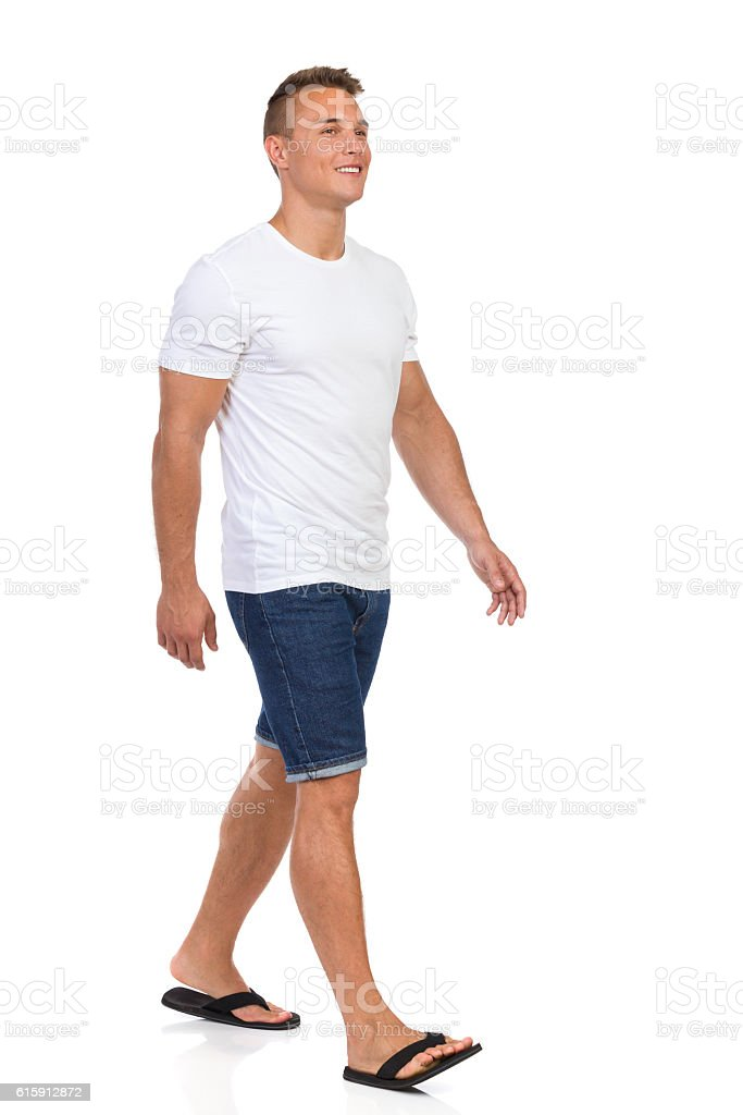 Smiling Man In White T-shirt Walking. Front Side View stock photo