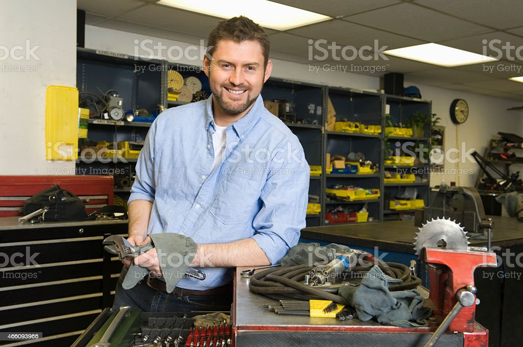 Smiling Man In Workshop With Tools stock photo