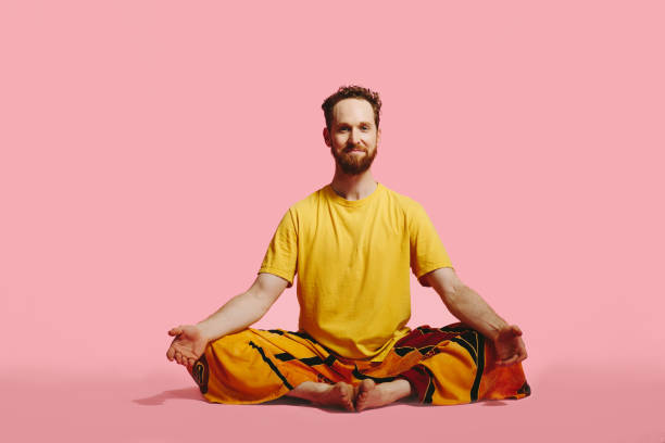 Smiling man in yoga position Full body portrait of a smiling man in a mediating yoga lotus position, looking at camera and isolated on white studio background cross legged stock pictures, royalty-free photos & images