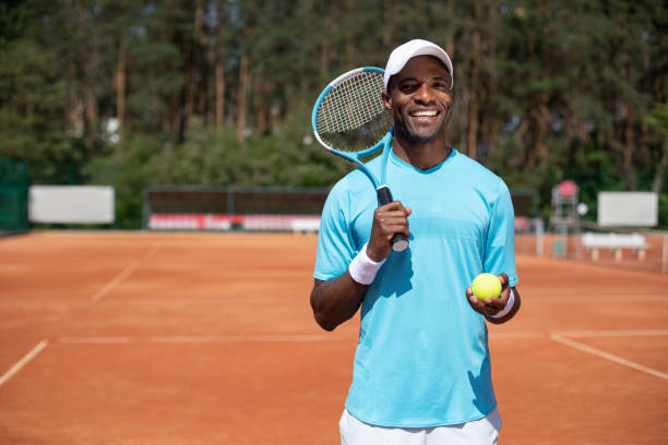 smiling man is going to play tennis outdoor - racket sport stock pictures, royalty-free photos & images