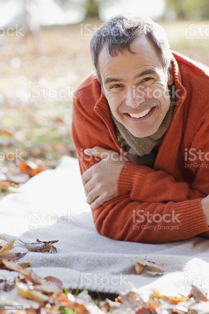Smiling man laying in park in autumn royalty-free stock photo