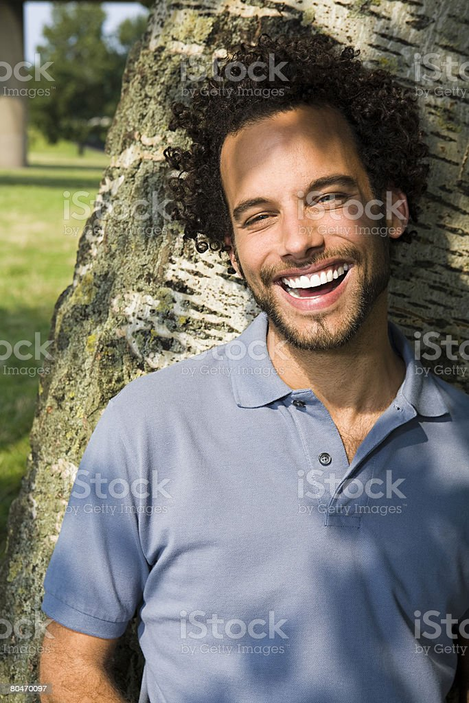 Smiling man leaning against a tree 免版稅 stock photo