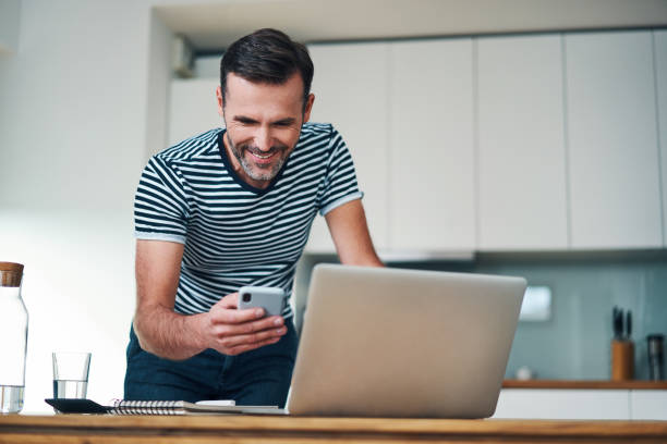 Smiling man leaning on desk in home office looking at laptop and smartphone stock photo