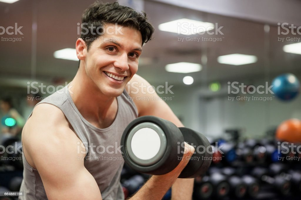 Smiling man lifting dumbbell weight foto stock royalty-free