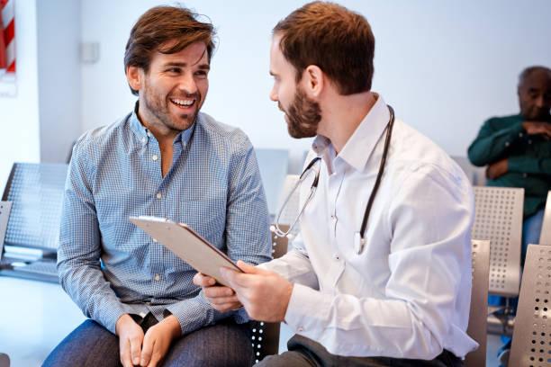 Lächelnde Mann schaut mit Zwischenablage auf Arzt – Foto