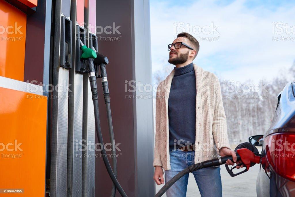 Homem sorridente, olhando para o medidor de combustível em posto de gasolina - foto de acervo