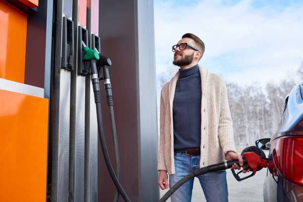 Smiling Man Looking at Fuel Meter at Gas Station stock photo