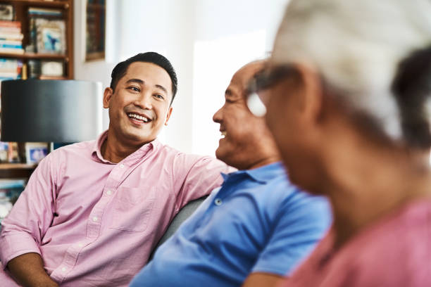 Smiling man looking at senior parents at home Smiling man talking while looking at senior parents in living room. Happy family is sitting on sofa. They are at home. old mother son asian stock pictures, royalty-free photos & images