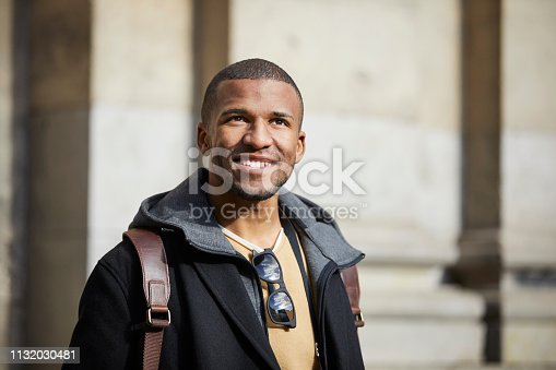 Smiling man looking away in city. Young male is exploring on sunny day. He is wearing casuals.