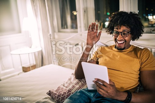 Young and handsome black student, holding a digital tablet while lying in bed, late at night.