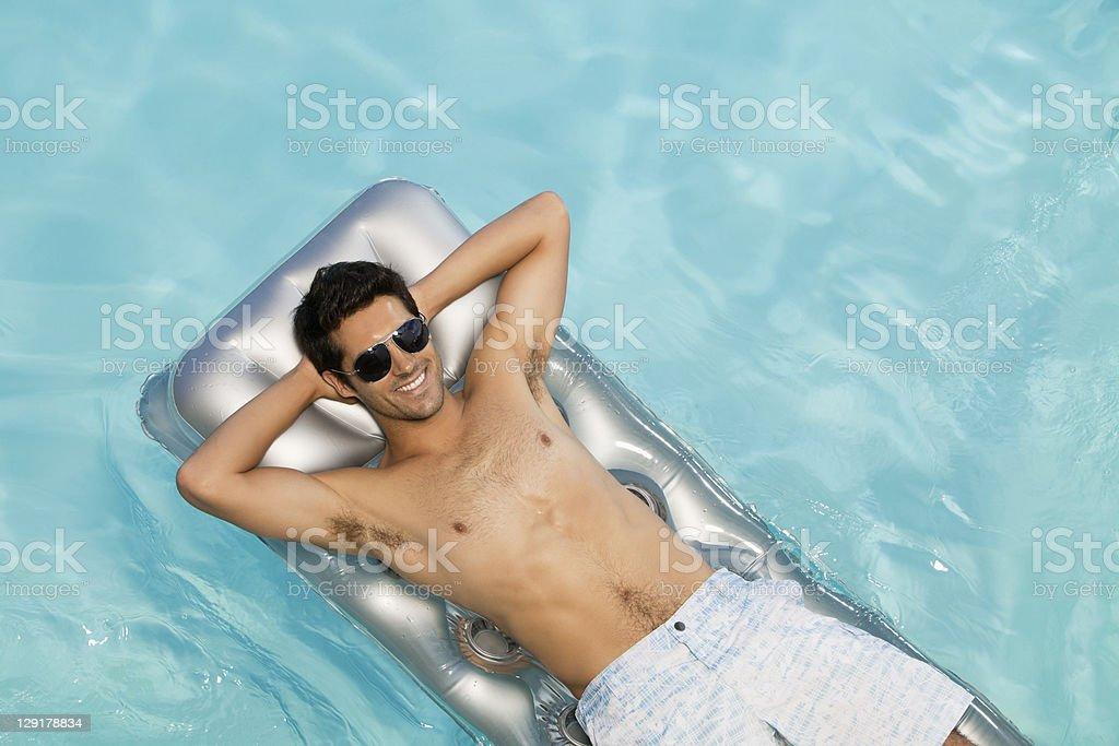 Smiling man lying on pool raft royalty-free stock photo