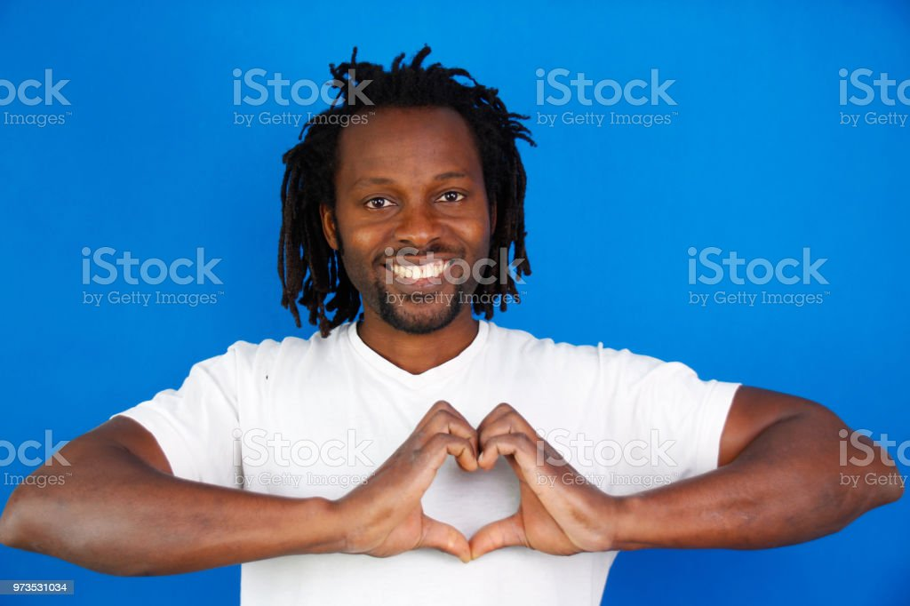 Smiling man makes love signs with his hands