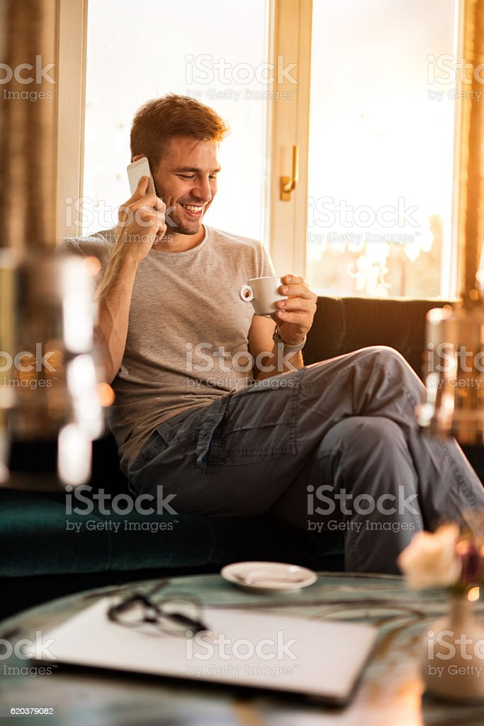 Smiling man making a phone call while drinking coffee. foto de stock royalty-free