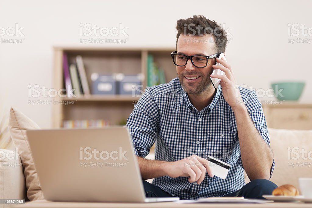 Smiling man making order by mobile phone stock photo