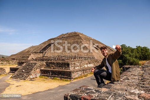 Smiling man discovering Mexican pyramids. He is making a selfie in front of pyramid of Sun