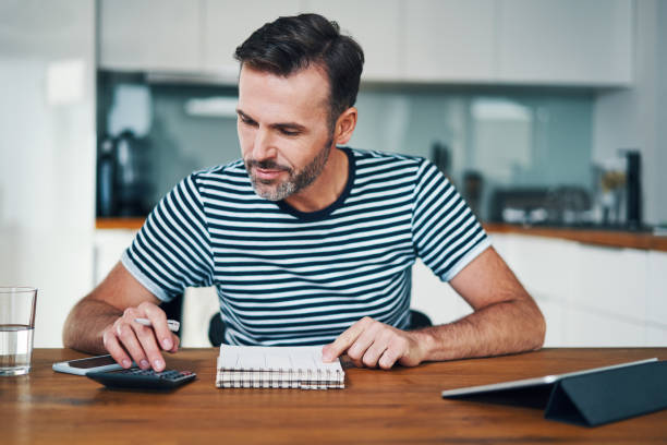 Smiling man managing home budget with calculator and notebook while sitting at dining table stock photo