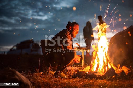 istock Smiling man next to a bonfire in the dark 1176619360