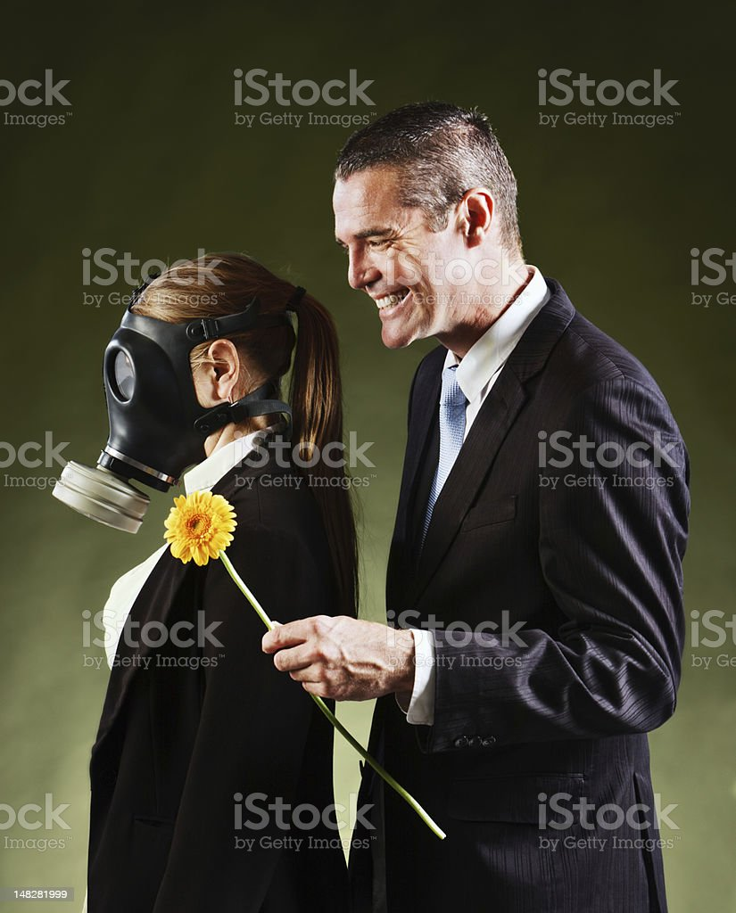 Smiling man offers woman in gas mask a flower stock photo