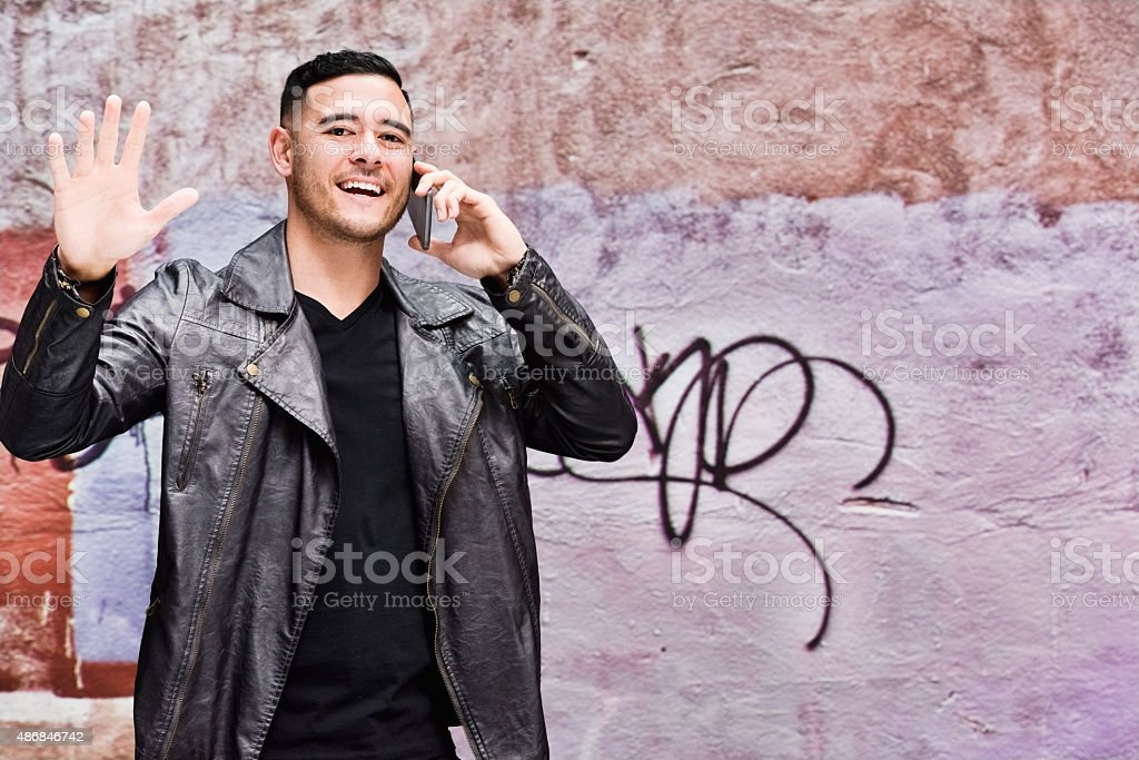 Smiling man on mobile and waving hand stock photo