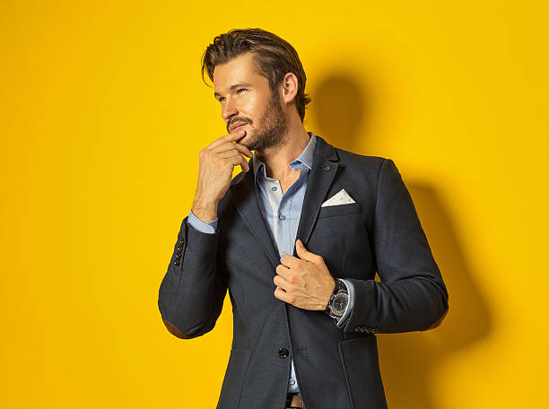 lächelnder mann auf gelbem hintergrund - lange jacken stock-fotos und bilder