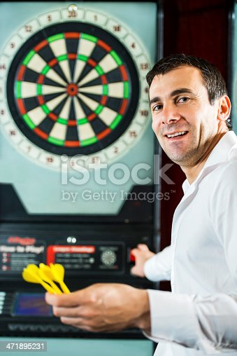 Smiling mid adult man having fun by playing darts and looking at the camera.
