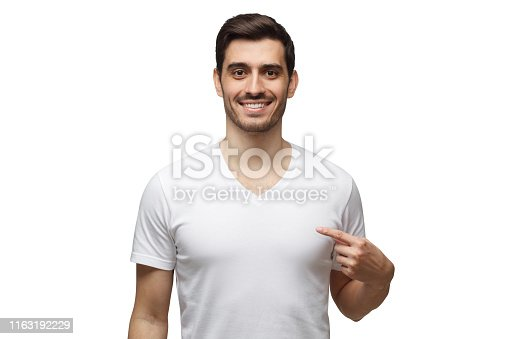 1093999692 istock photo Smiling man pointing at his blank t-shirt with index finger, copy space for your advertising, isolated on white background 1163192229